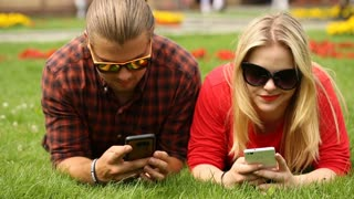 Absorbed couple lying on the grass and texting on smartphones