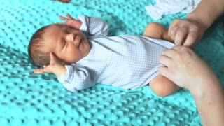Adorable newborn baby crying while his mother dressing him