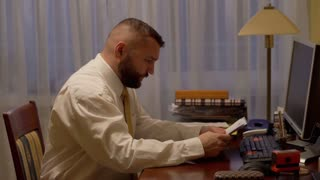 Angry businessman scatters documents on the desk at work in home office