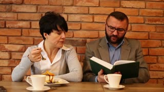 Angry couple sitting in cafe, businessman reading a book