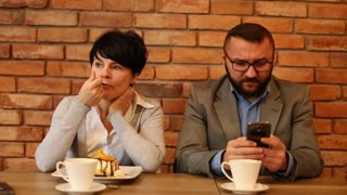 Angry couple sitting in cafe, businessman writing sms