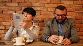 Angry couple sitting in cafe, businesswoman with tablet