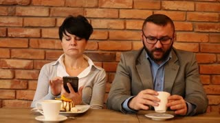 Angry couple sitting in cafe, businesswoman writing sms