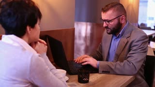 Angry couple with laptop sitting in cafe