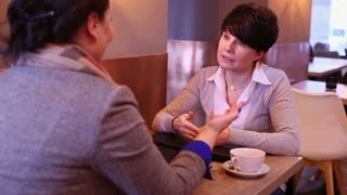 Angry, irritated women arguing in cafe