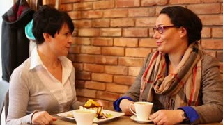 Angry, unhappy women arguing in cafe