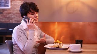 Angry woman sitting at caffe and talking on cellphone