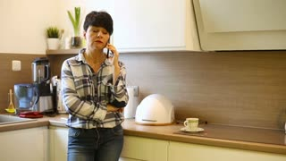 Angry woman standing in the kitchen and having a quarrel while speaking on phone