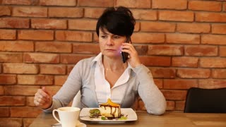 Angry woman talking on cellphone by the table at caffe