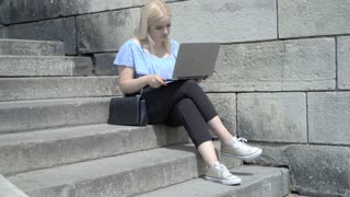 Asborbed girl sitting on the stairs in the city and using laptop
