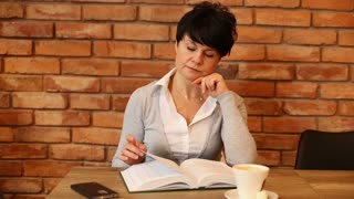 Attractive, absorbed woman reading book in the cafe