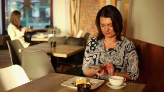 Attractive smile woman texting, sending sms on smartphone in cafe