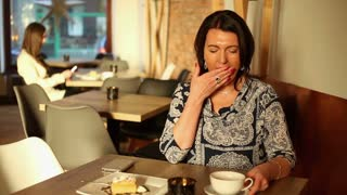Attractive tired women yawn in cafe