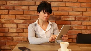 Attractive woman having headache during work with tablet at caffe