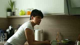 Attractive woman leaning on worktop in the kitchen and talking to someone