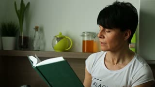 Attractive woman looks interested while reading book in the kitchen