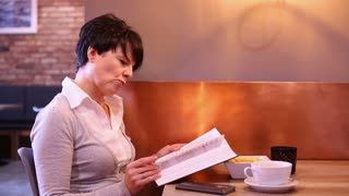 Attractive woman reading book in the cafe