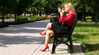 Attractive woman sitting in the park and applies mascara on her lashes