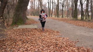 Attractive woman with documents, walking in the autumnal park and waving