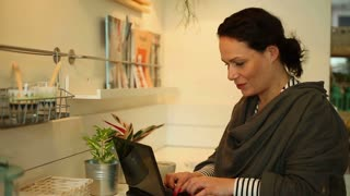 Attractive woman with laptop sitting in cafe, close