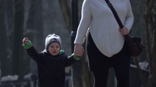Baby boy walking with his mother in zoological garden and crying, slow motion shot at 240fps