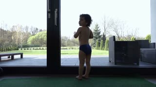 Baby boy wearing panties and standing next to the window, slow motion shot at 240fps