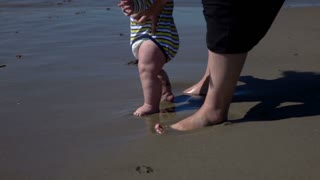 Babys and mothers feets standin on the beach, super slow motion