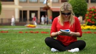 Blonde girl in red shirt sitting on the grass and reading book
