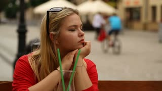 Blonde girl looks sad while sitting in the restaurant and drinking juice