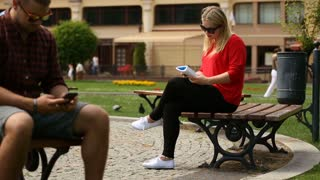Blonde girl sitting on the bench in the city and reading book