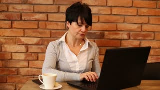 Bored businesswoman working on modern laptop in cafe