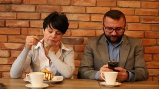 Bored couple sitting by the table at cafe, man writing sms