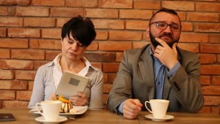 Bored couple sitting by the table at cafe, woman with tablet