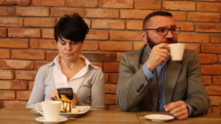 Bored couple sitting by the table at cafe, woman writing sms
