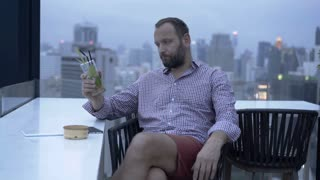 Bored man sitting on the building's roof and drinking alcoholic drink