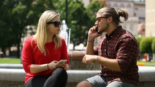 Boy looks angry while speaking on cellphone and sitting with his girlfriend next