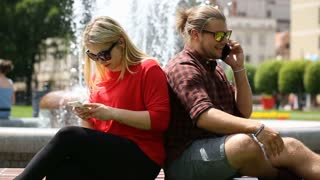 Boy looks angry while speaking with someone on cellphone and leaning on his girl