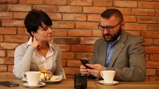 Business couple watching funny things on smartphones in cafe