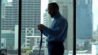 Businessman getting ready for work in his apartment, slow motion shot at 240fps
