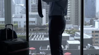 Businessman getting ready for work in his hotel room and ties a tie