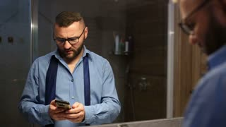 Businessman looks angry while speaking on cellphone with someone in the bathroom