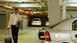 Businessman opens his car and packing his things into car's trunk