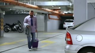 Businessman packs luggage to car's trunk and leaving