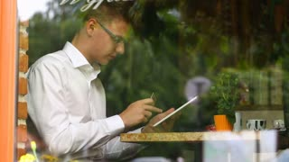 Businessman sitting behind cafe's window and doing online shopping