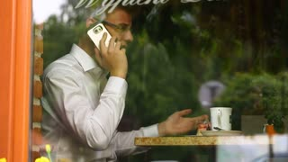 Businessman sitting behind cafe's window and looks angry while speaking on cellphone