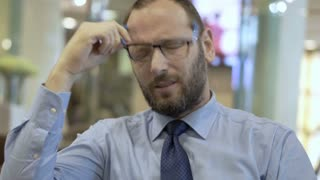 Businessman sitting in the cafe and having painful headache