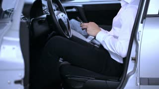 Businessman sitting in the car and texting messages on smartphone