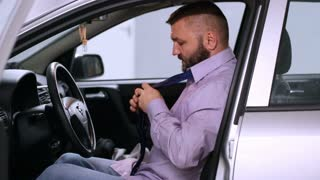 Businessman sitting in the car and tie a tie
