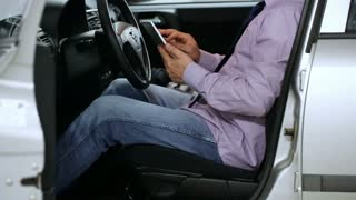 Businessman sitting inside his car and browsing internet on smartphone