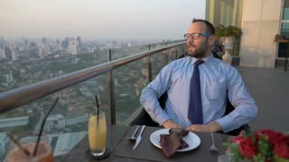 Businessman sitting on the rooftop during dinner and enjoying the view